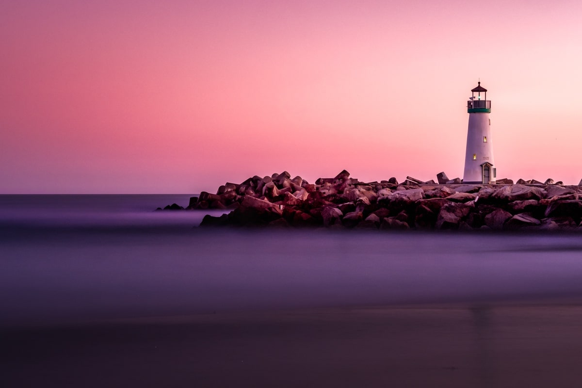 lighthouse set against a pink sky at sunrise