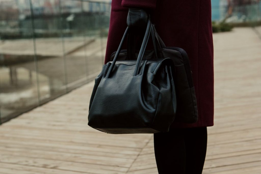 Close up of expensive leather handbag carried by woman with maroon coat